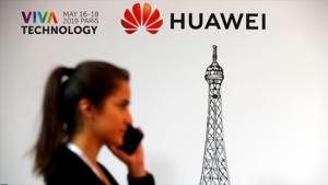 Cartel de una feria tecnológica con el logo de Huawei, delante hay una mujer