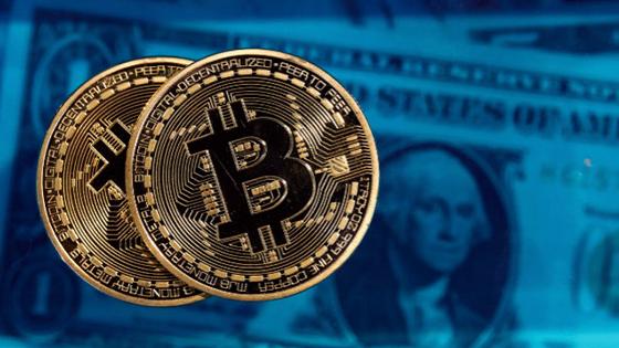Dos bitcoin en primera plana y en el fondo un dolar